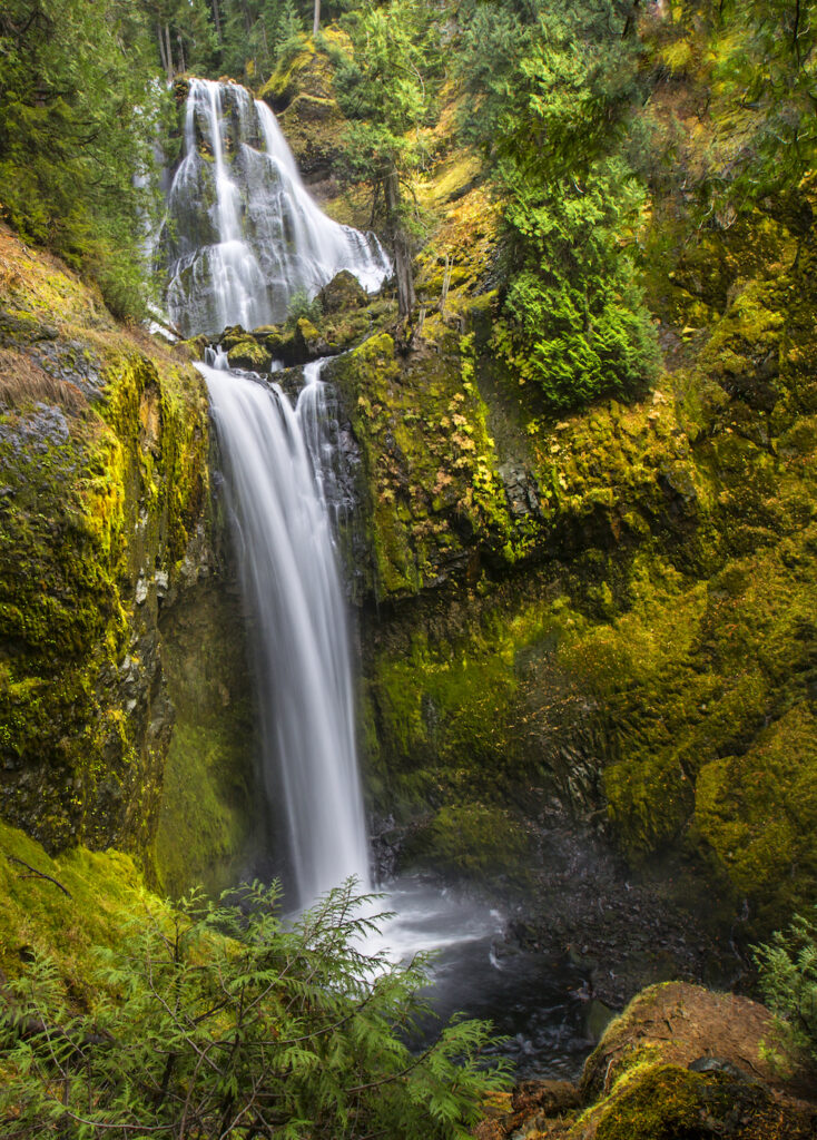Multiple tiers of a famous waterfall in Washington State, plunging into a pool of water below, framed by forest foliage.