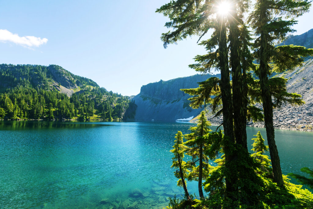 bright blue water of serenity lake in washington state with trees in the foreground