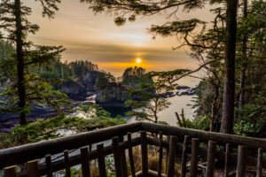 sunset over the pacific ocean in olympic national park, as seen from a wooden deck. olympic national park is one of the best road trips from seattle washington.