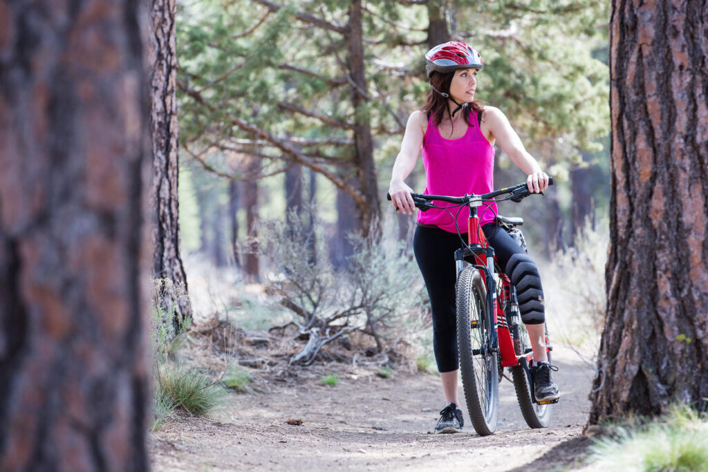 woman in a pink tank top rides a mountain bike along a trail lined with pine trees, one of the best things to do in bend or