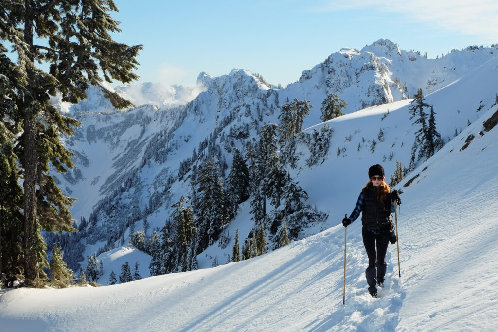 woman with 2 trekking poles hiking washington gothic basin in the snow