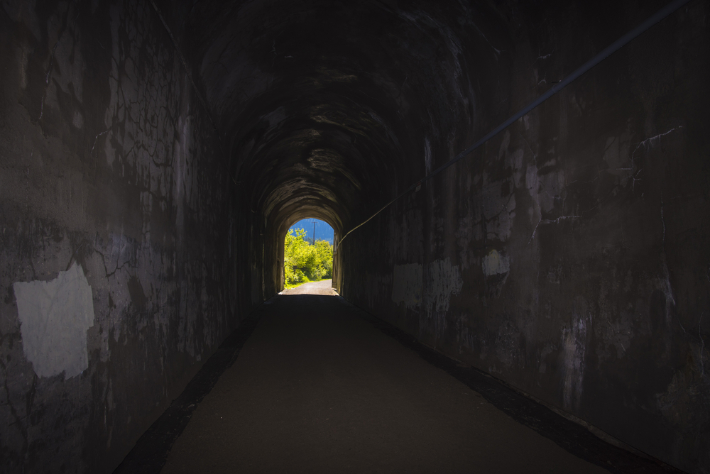 View from down the tunnel of Snoqualmie Tunnel with light at the end of the tunnel with forest