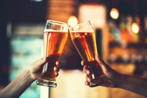 two beers being held up to toast. craft breweries are among the best things to do in bend or