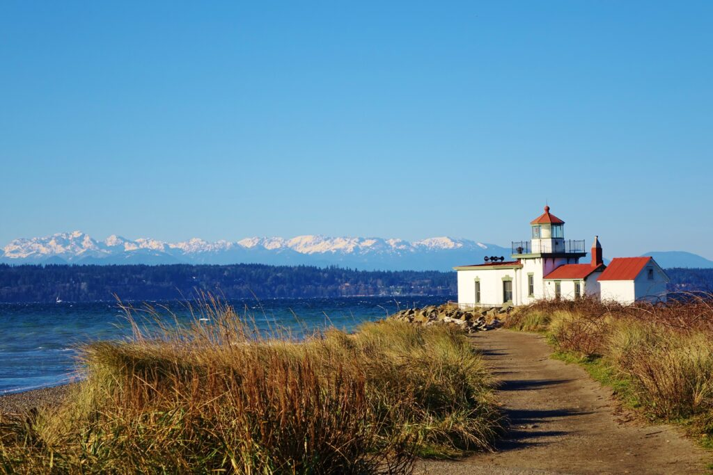 view of the lighthouse at discovery park, one of the best hikes near seattle wa. the view is from the trail with mountains visible in the distance