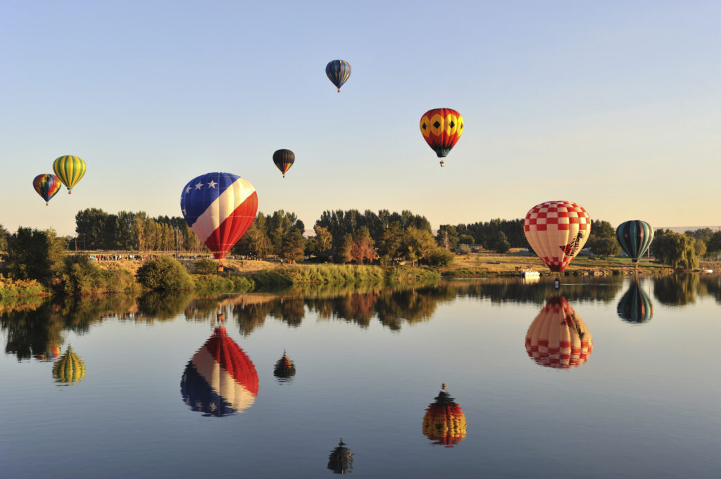 hot air balloons rising over a lake in prosser washington and reflecting into the water below