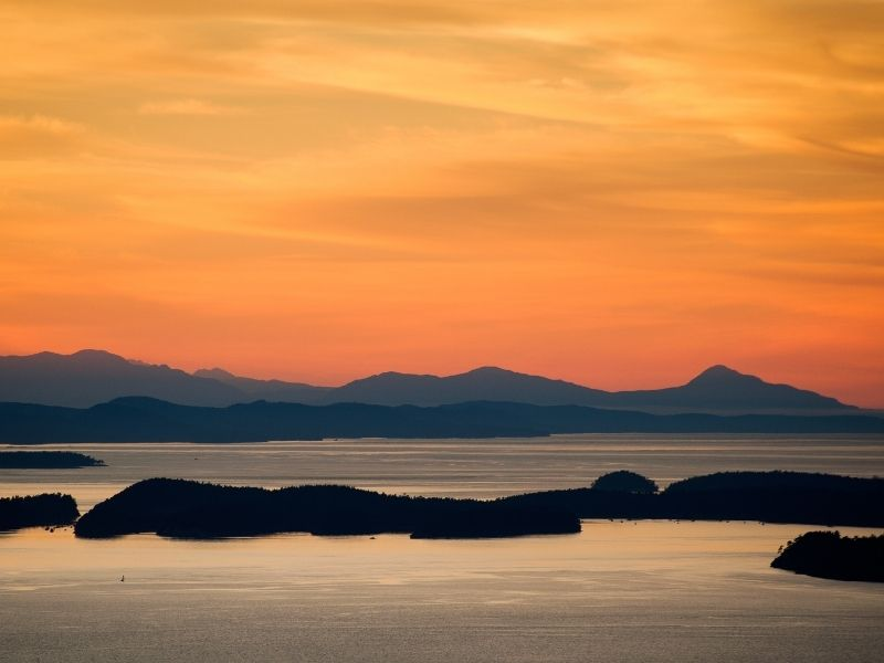 A sunset photograph of the San Juan Islands in Washington State with bright orange sky and shadowed islands.
