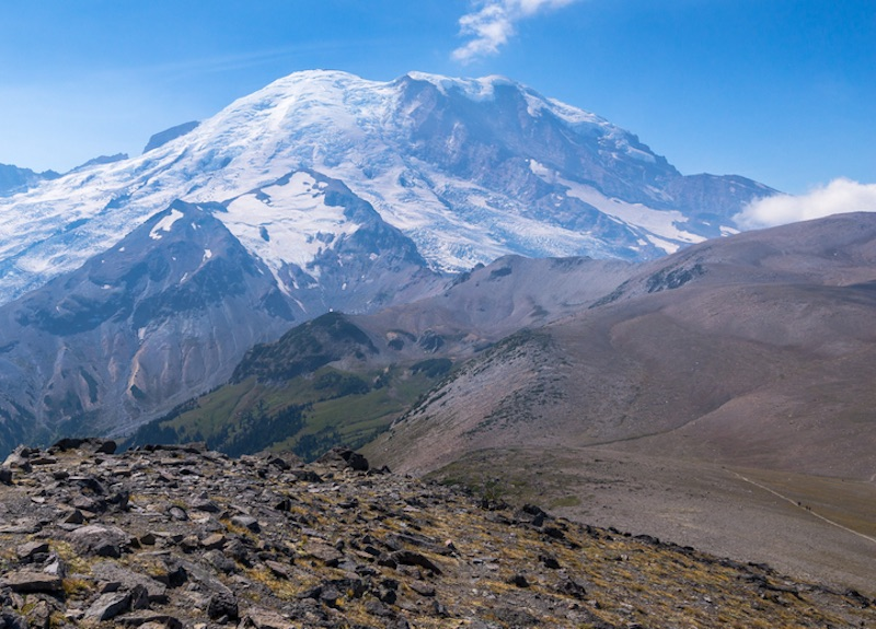 A rocky, barren trail landscape with a brilliant view of Mt Rainier covered in snow and ice in the distance.