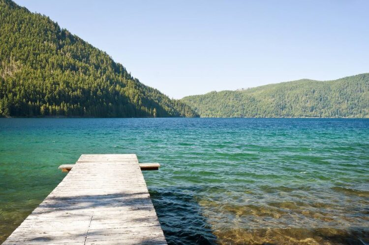 A small wooden pier leading out to brilliant blueish-turquoise lake water, surrounded by pine-tree covered mountains.