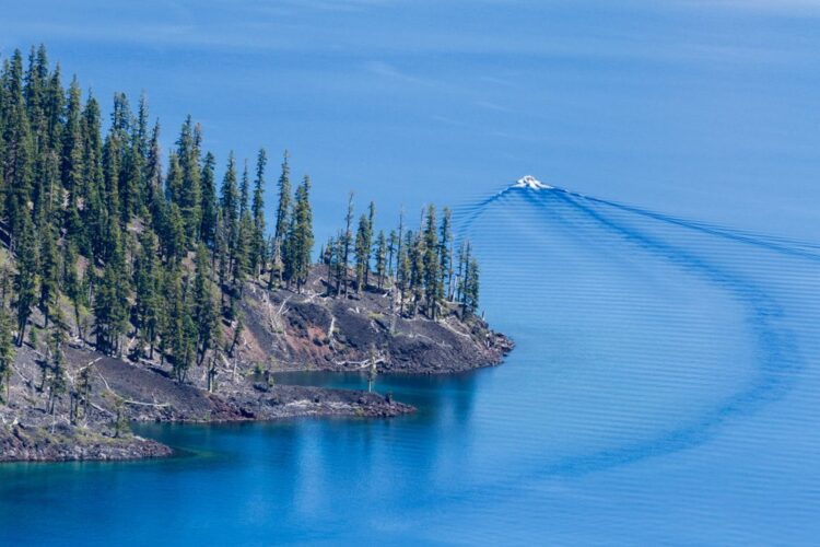 A boat passing by the edge of Wizard Island, a tree-covered small island, in Crater Lake.