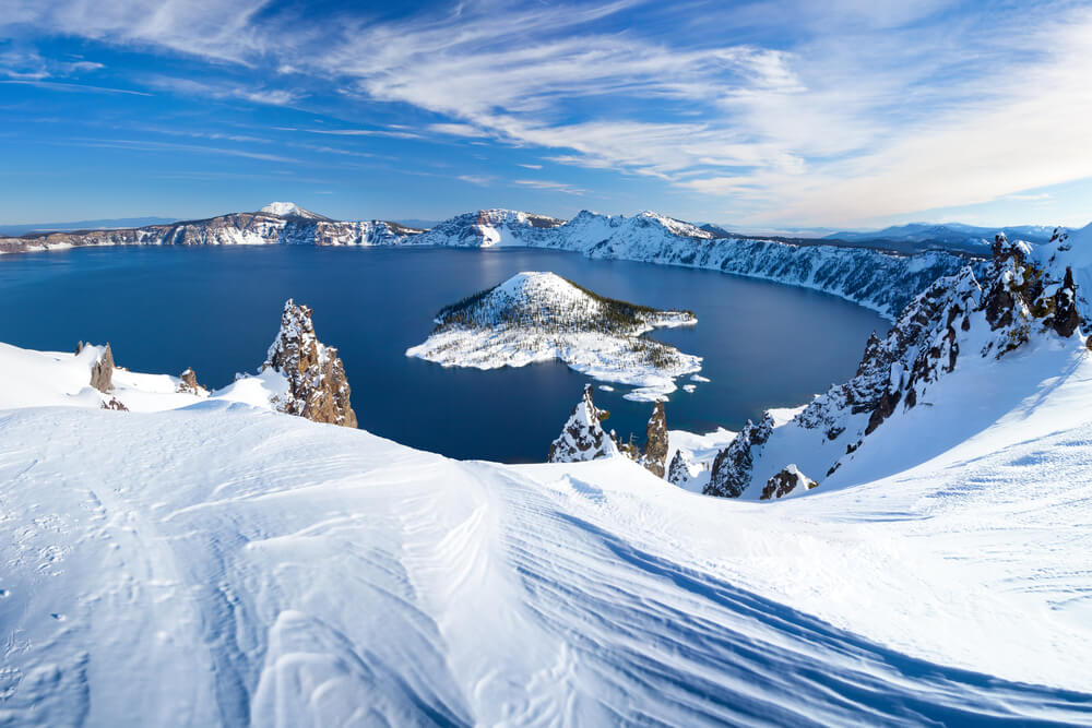 A snow-covered landscape of Crater Lake National Park in winter with a view of the famous island in the middle of a deep blue lake