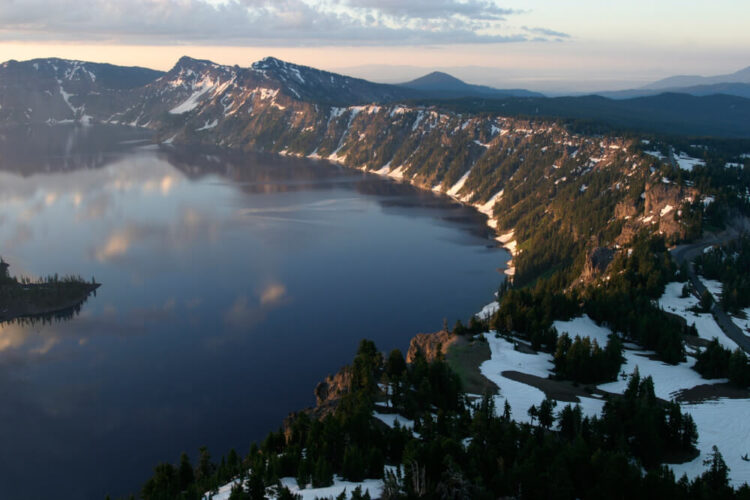 View of the lake from up on the caldera rim, with snow and trees and a view of a bit of the island in the middle of Crater Lake, with some light snow on the ground in winter. Sunrise or sunset.