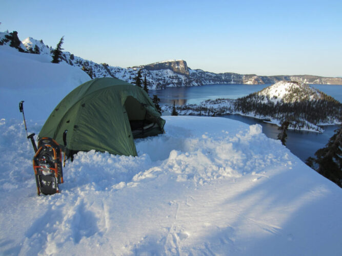 A tent perched in the snow, next to a pair of of snowshoes, overlooking Wizard Island covered in snow in the middle of Crater Lake in winter.