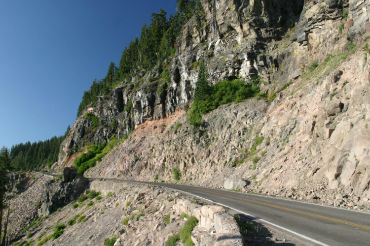A two-lane road circling Crater Lake cut out from the cliff edge with a steep drop off to the side.
