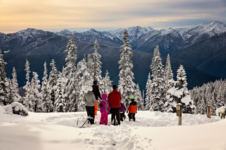 A family of six enjoying a beautiful view of the snow-covered mountains in Olympic National Park in December
