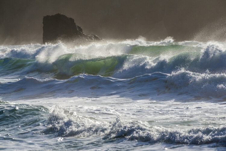 Close up shot of wild surf crashing around a sea stack in the Pacific Ocean near Olympic National Park in the winter time.