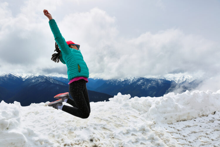 A young woman in a turquoise jacket jumping for joy in the snow near Hurricane Ridge.