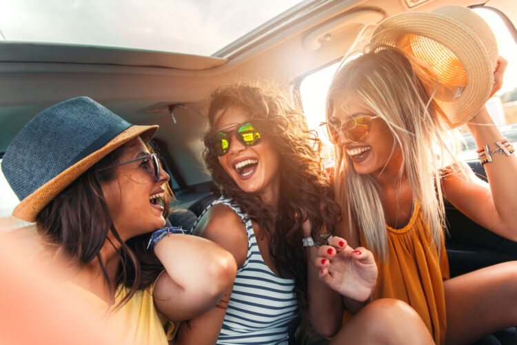 group of young women laughing in the backseat of a car on a road trip
