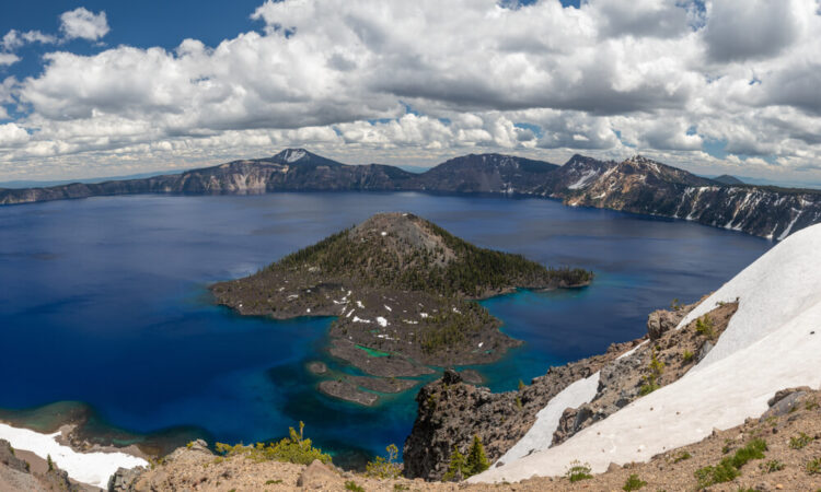 View of the island in the middle of Crater Lake, Wizard Island, surrounded by blue and teal water, seen from an overlook covered in light snow.