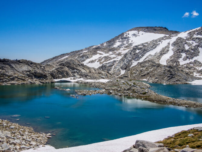 Brilliant blue lake water surrounded by rocks and some snow that has yet to melt.