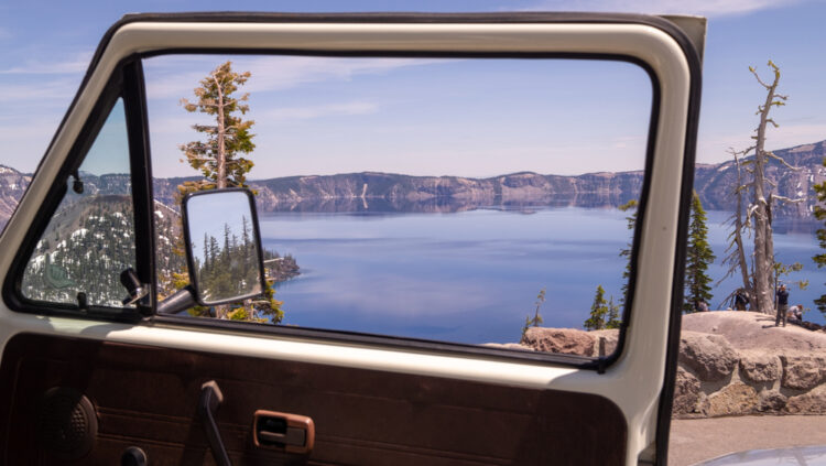 An open car door showing the Crater Lake through the open window, the reflection in the rearview mirror shows some pine trees. A man is standing on a rock taking a photo of the lake in the distance.
