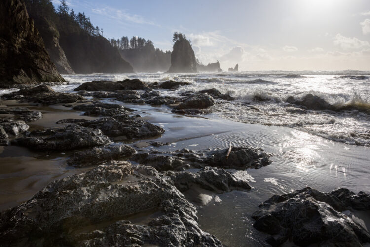 Empty beach with a rocky, sandy shore with wild waves and rock formations off in the distance as well as cliffs.