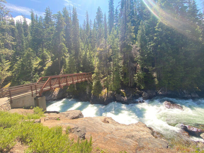 A rushing creek with a bridge to cross it, with a trail going through the trees on a sunny day in Leavenworth hiking