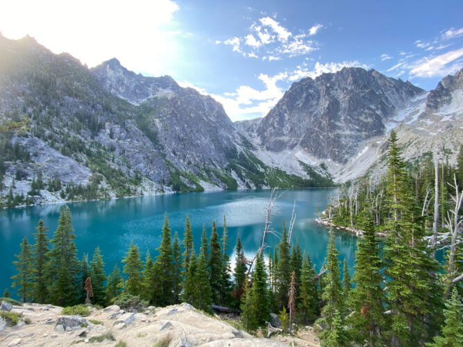 A turquoise blue lake, surrounded by evergreen trees, as well as towering mountains with cragged peaks. Sunburst in the top left corner.