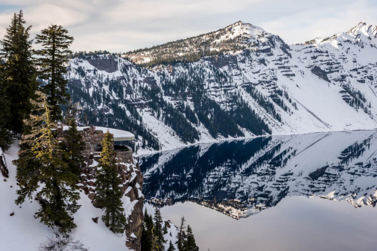 View of the mirror effect of Crater Lake as it reflects a snow-covered mountain with soft morning light from an overlook in the park