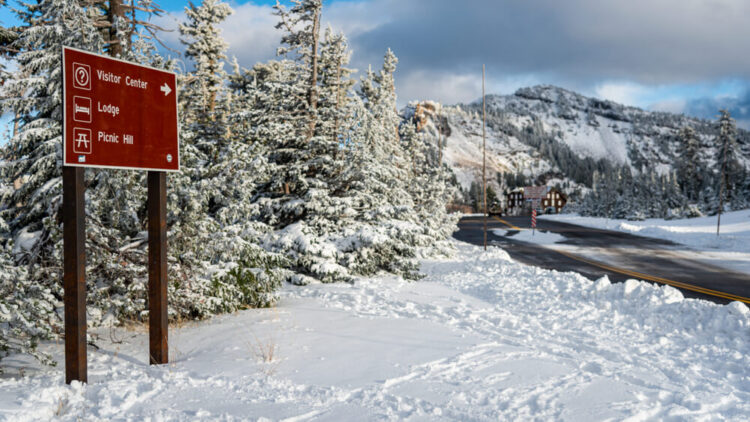 """A sign reading """"Visitor Center, Lodge, Picnic Hill"""" surrounded by snow, a plowed road leading to buildings off in the distance."""