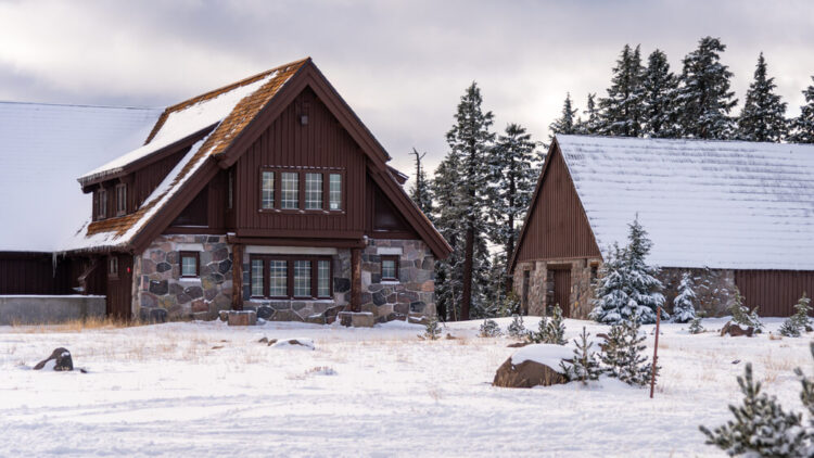 View of stone and wood buildings covered in snow, in a snowy landscape in Crater Lake in winter by the visitor center.