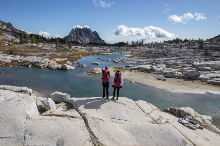 Two well prepared female hikers, wearing pink backpacks, looking out at the Upper Enchantments landscape of a creek and rocks, planning their hike in the Enchantments