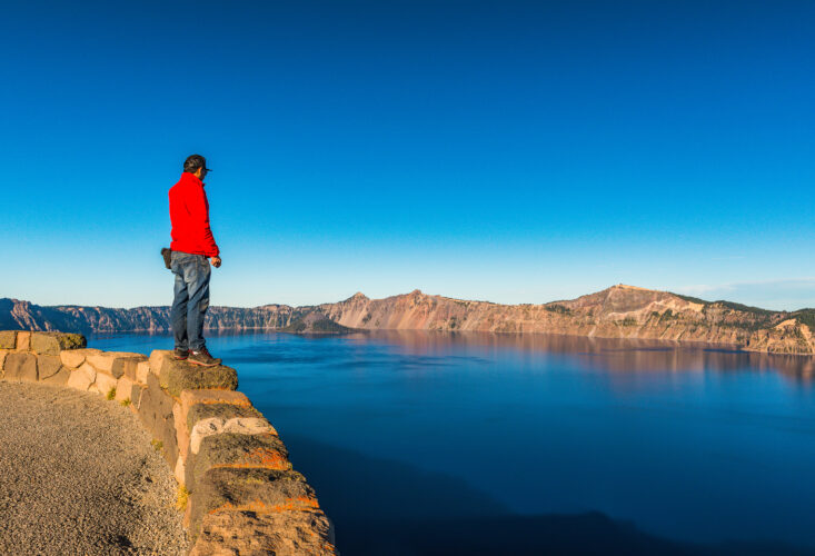 man overlooking crater lake from rim