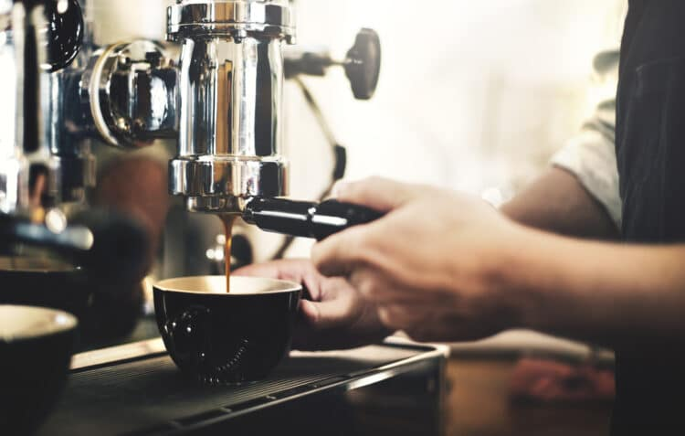 espresso being pulled into a black cup