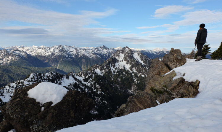 Female hiker wearing snow boots, parka, and hat, standing on the edge of a snowy mountain in Olympic National Park in winter.