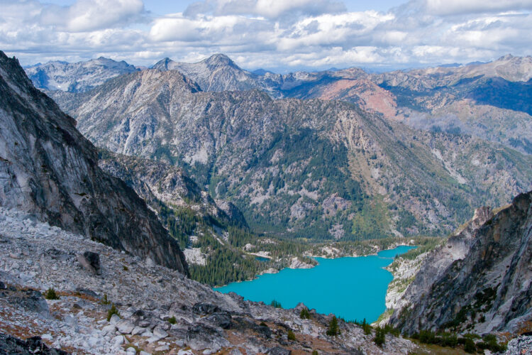 A view of Colchuck Lake as seen from Aasgard Pass: a brilliant turquoise lake fringed by green trees in the middle of towering mountain ranges.