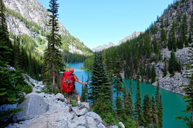Male hiker wearing an orange baseball hat and shorts, carrying trekking poles and a big red backpack, looking into one of the many turquoise blue alpine lakes in the Enchantments hiking wilderness.