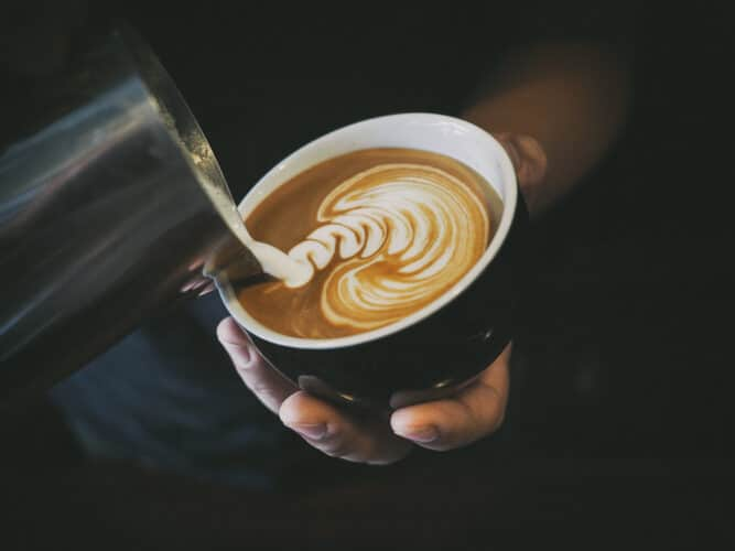 hand of a barista pouring steamed milk into a latte