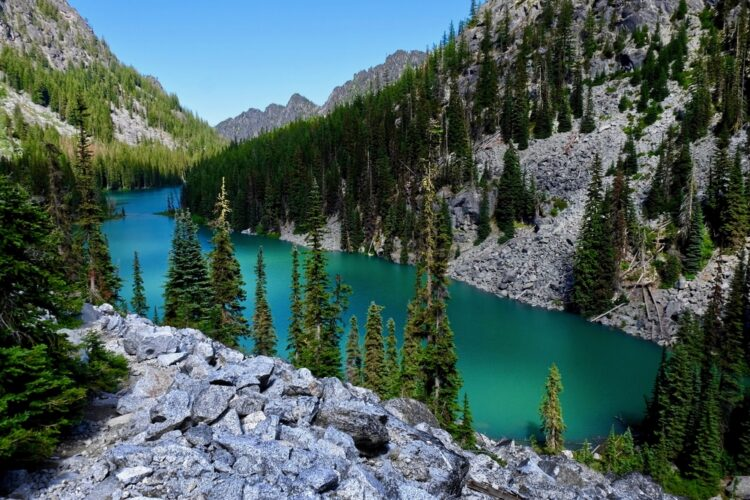 The brilliant turquoise, almost green, Nada Lake surrounded by rocks and evergreen trees in the Enchantments wilderness area.