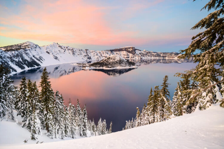 View of Crater Lake from seen from above at sunset or sunrise with pastel colors above the lake