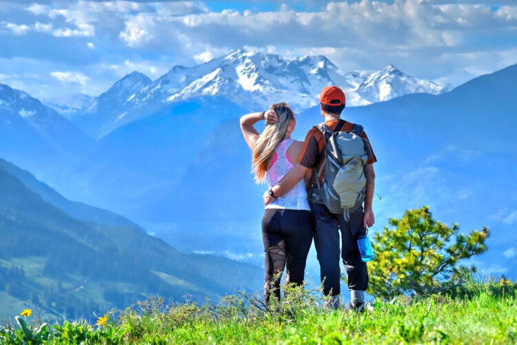 couple standing in a meadow overlooking mountains when hiking in north cascades national park