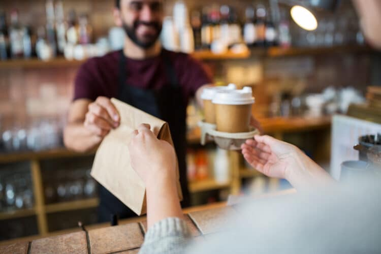 barista handing over coffee and a brown bag with pastry to go