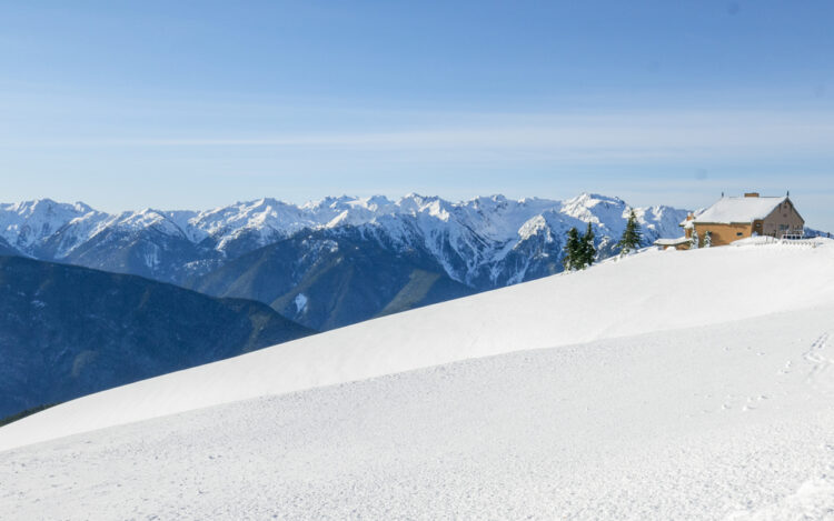 The Hurricane Ridge visitor center in Olympic National Park in the winter surrounded by snow and snow-covered mountains.
