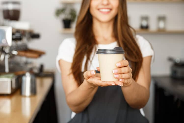 young woman working at a bend or coffee shop holding out a to-go cup of coffee
