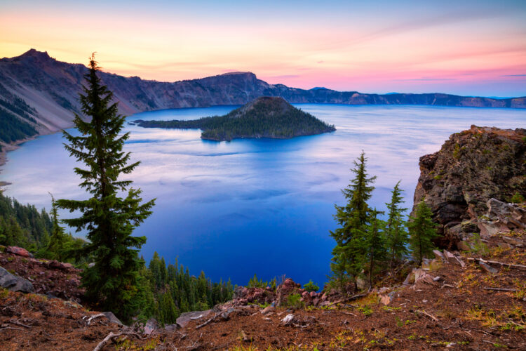 A deeply saturated view of Crater Lake at sunset, with deep blue water, orange and purple sky, and a small island in the middle of the lake.