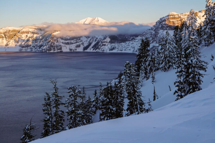 View of Crater Lake at sunrise, with snow-covered rim, some low-lying clouds on part of the caldera, and alpenglow (pink tinged peaks) from the morning sun on a few select ridges.