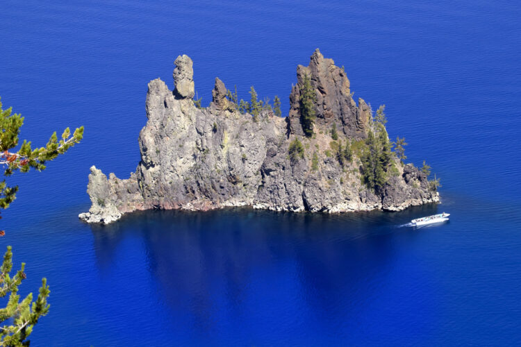 Brilliant deep cerulean blue water with a small white boat the base of Phantom Ship island, a small island in the middle of Crater Lake