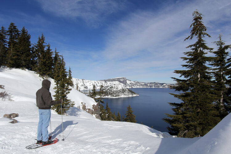 A man in a hoodie and jeans wearing snowshoes looking out onto a snow-covered Crater Lake winter landscape, including Wizard Island covered in snow, on a sunny day.