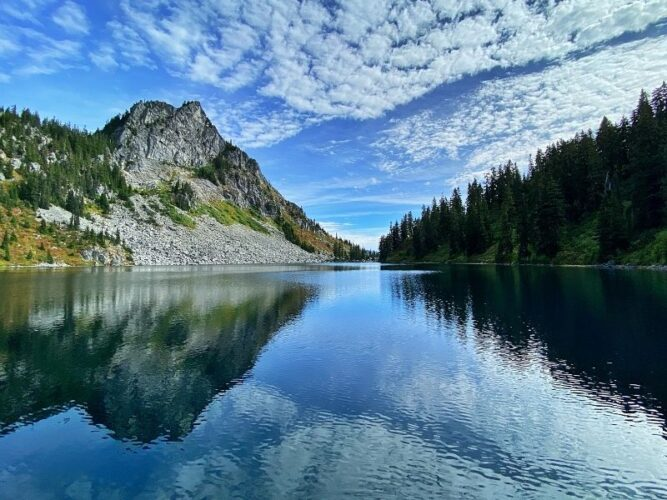 Lake water reflecting pine trees on one side and a rocky mountain on the other on a partly cloudy day.