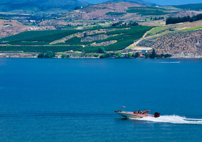 A group of people out on a speed boat in Lake Chelan, with another speed boat way off in the distance, on the lake shores are agricultural fields and other flora.