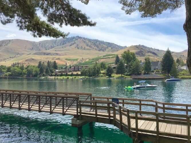 Boardwalk over the turquoise water of Lake Chelan with two boats in the distance, someone swimming in water, and hills in the distance.